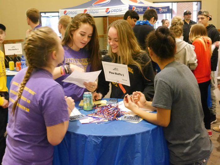 Four students standing at a table participating in a JA activity