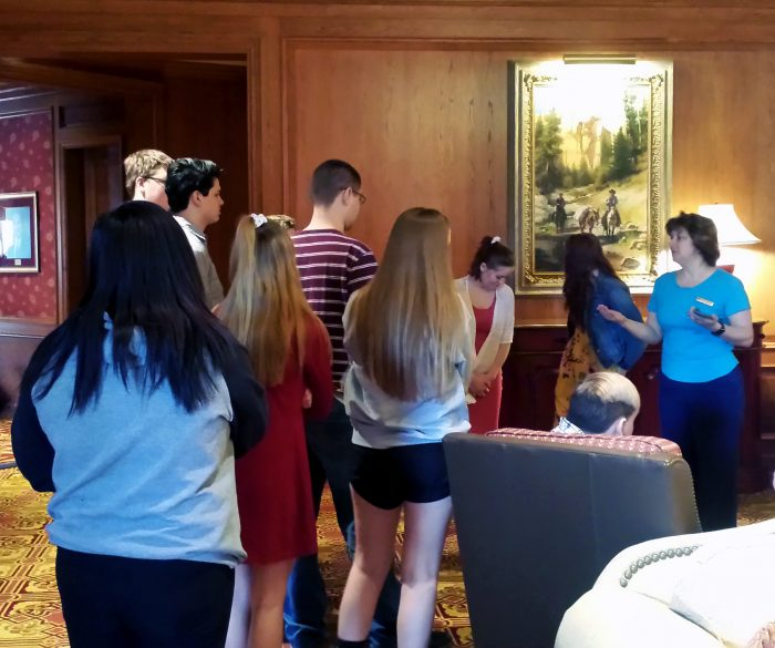 High school students gather in the lobby with a Little America employee
