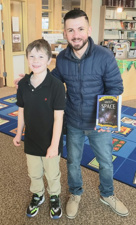Mariano with student in library holding  b ook