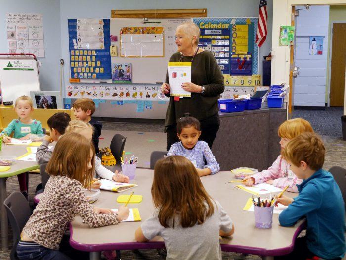 Susan Zapata in front of a kindergarten classroom teaching JA