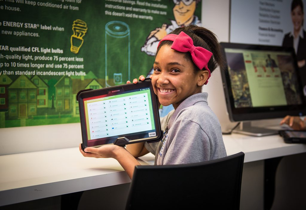 Economically disadvantaged female student holding tablet, smiling, with bow in her hair