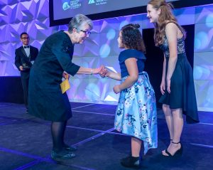 Judith Wagner shaking hands with 2 JA students on stage at the 2020 Colorado Business Hall of Fame.