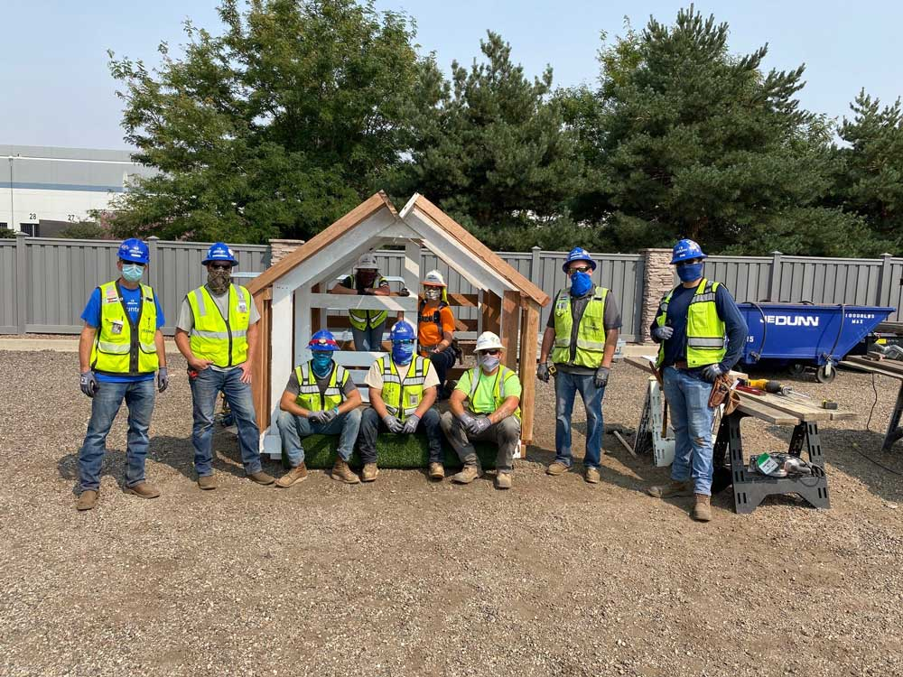 JE  Dunn construction team standing in front of the playhouse they created for Parade of Playhouses