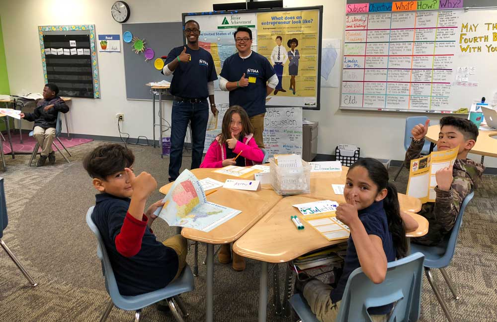 TIAA volunteers inside classroom with elementary kids