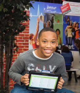 boy sitting holding up a tablet with JA Finance Park program