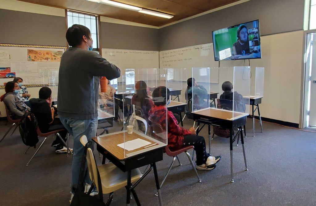 Native American students standing and sitting at St. Stephens Indian School participating in JA virtual programs.